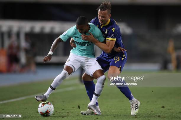 Hellas Verona's Kosovan defender Amir Rrahmani grapples with Inter's English midfielder Ashley Young during the Serie A match between Hellas Verona...