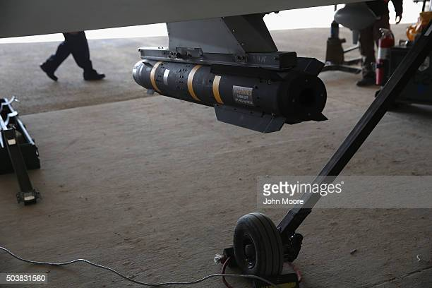 Hellfire missile hangs from a US Air Force MQ1B Predator unmanned aerial vehicle at a secret air base in the Persian Gulf region on January 7 2016...