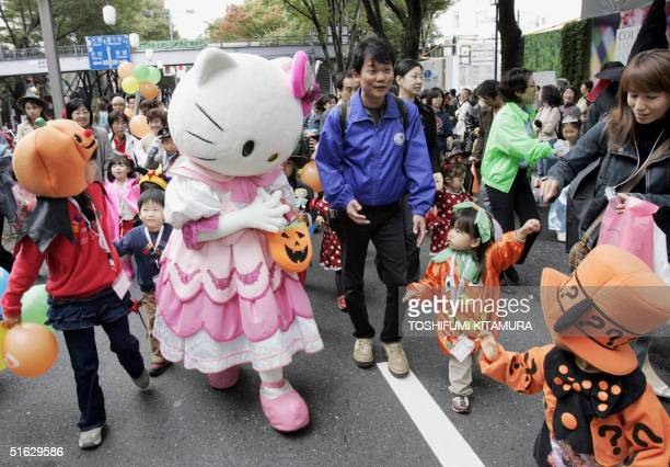 Hello Kitty the hugely popular cartoon cat greets children while attending a Halloween parade in the Omotesando district of Tokyo 31 October 2004...