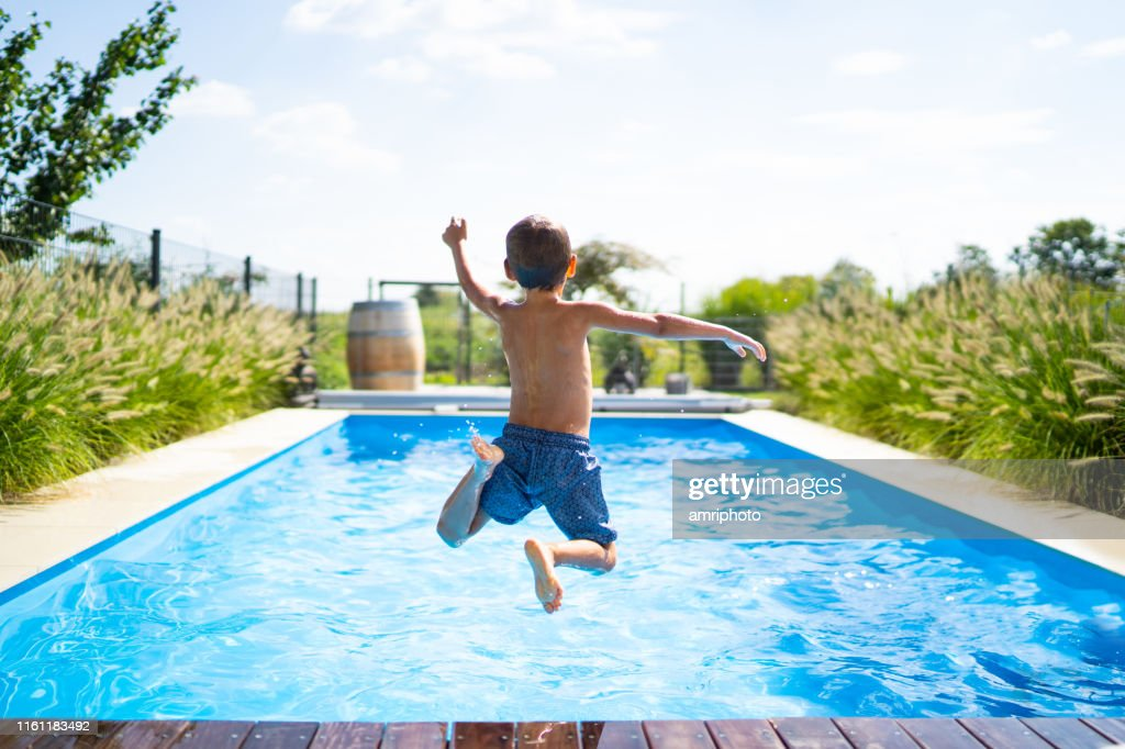 hello summer holidays - boy jumping in swimming pool : Stock Photo