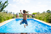 hello summer holidays - boy jumping in swimming pool