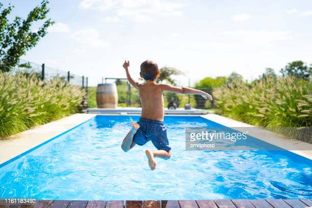 hello summer holidays - boy jumping in swimming pool - bagnato foto e immagini stock