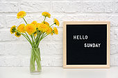 Hello Sunday words on black letter board and bouquet of yellow dandelions flowers on table against white brick wall. Concept Happy Monday. Template for postcard
