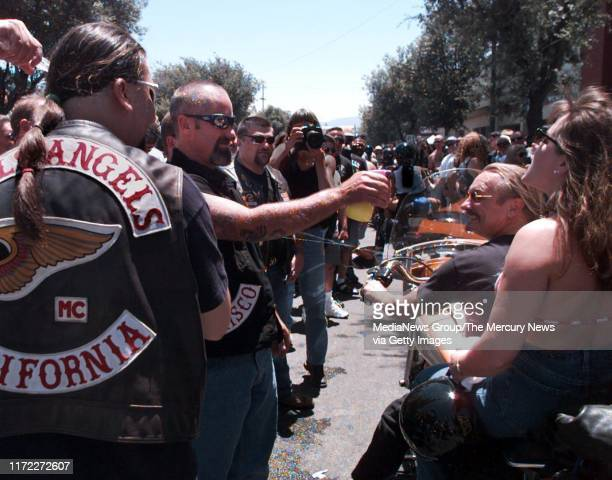 Hells Angels from San Francisco use spray bottles to provide welcome relief from the heat for bikers on San Benito Street in Hollister. [970705 FR 1A...