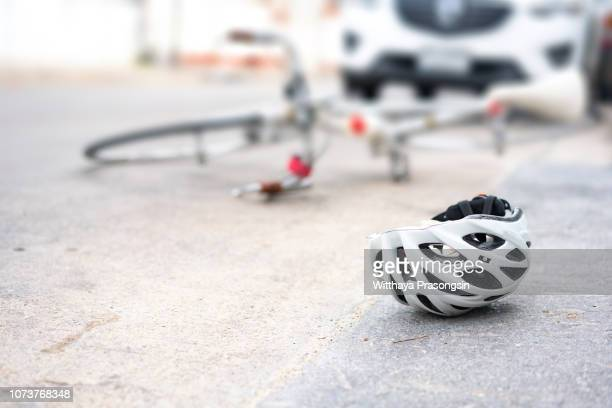 helmet and bike lying on the road after a car hit a cyclist on a pedestrian crossing - accidente moto fotografías e imágenes de stock
