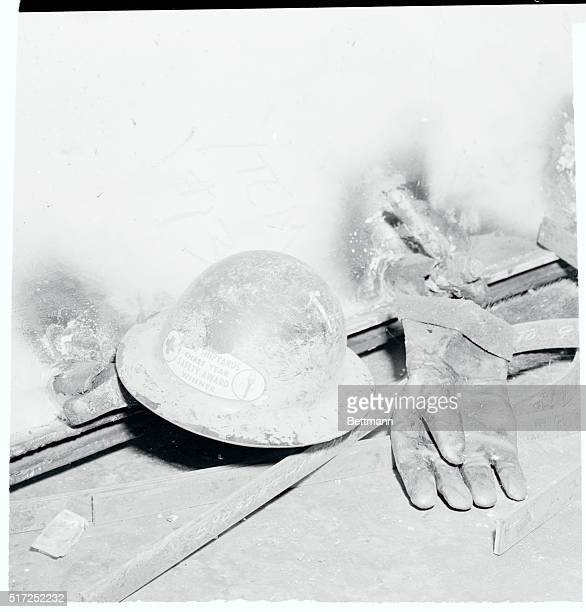 A helmet ironically bearing a safety award symbol and a glove belonging to Leon Evans of Oakland California lie against a hatch cover after Evans was...