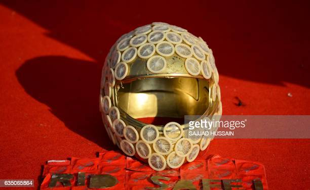A helmet is decorated with condoms during an event to mark International Condom Day in New Delhi on February 13 2017 The event was organised by AIDS...