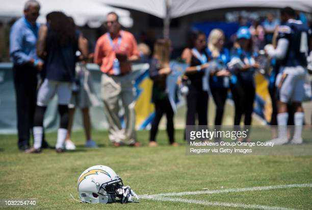 A helmet lies on the ground as players sign autographs in the background after the Chargers' training camp at the Jack Hammett Sports Complex in...