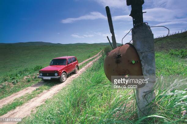 Helmet with bullet holes abandoned on the side of a dirt road near Martuni, front line during the Nagorno-Karabakh war , Azerbaijan, 20th century.