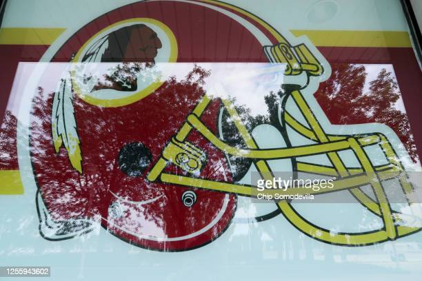 A helmet with the NFL Washington Redskin's logo decorates a window at FedEx Field July 13 2020 in Landover Maryland The team announced Monday that...