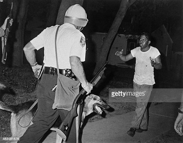Helmeted police riot argue with an African american man as Newark witnessed its second night of rioting on July 14 1967 / AFP /