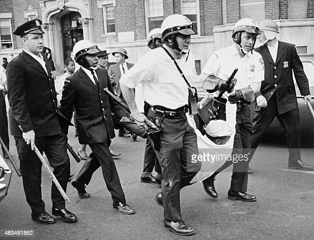 Helmeted police riot guards drag a rioter away from the scene of violence in Newark after New Jersey's largest city witnessed a second night of...
