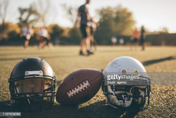 nfl helmets and ball on grass on training - ncaa stock pictures, royalty-free photos & images