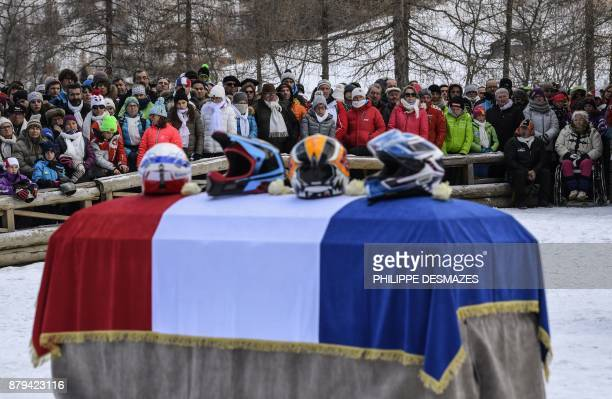 Helmets are placed on the flagdraped coffin of late French skier David Poisson as people attend a ceremony in his memory in PeiseyNancroix in the...