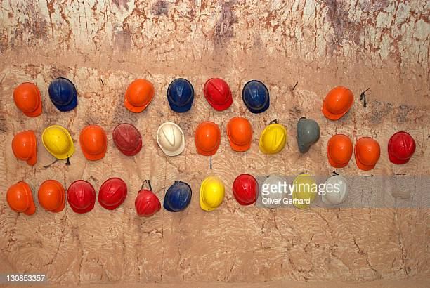 Helmets hanging at a stone wall in an opal mine, Coober Pedy, South Australia, Australia