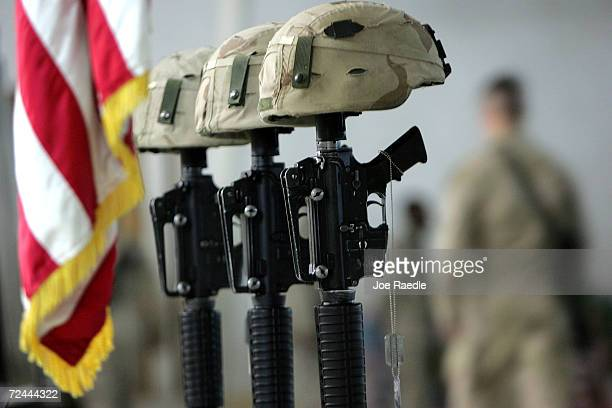 Helmets rest on weapons as the dog tags of US Army soldiers hang from them during a memorial ceremony for three soldiers from 1st Battalion 503rd...