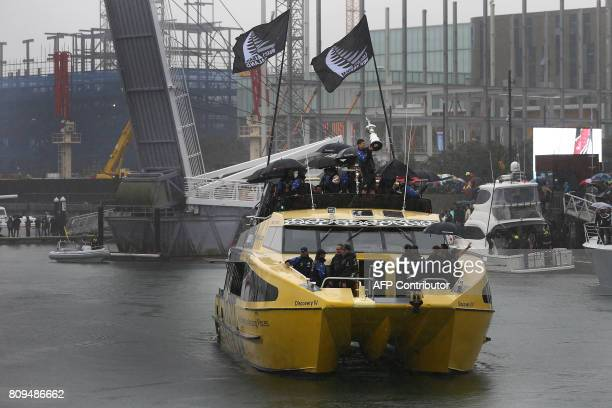Helmsman Peter Burling holds up the America's Cup yachting trophy on a boat as members of the Emirates Team New Zealand participate in a victory...