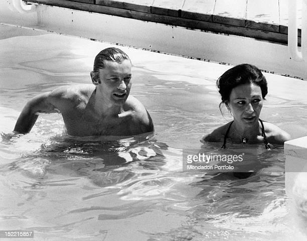 Helmut Berger and Flora Carabella bathe in a swimming pool Taormina 1973