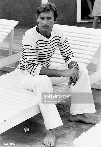 Helmut Berger poses barefoot sitting on a sunbed Taormina 1973