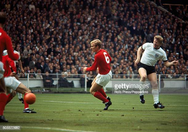 Helmut Haller shoots past England captain Bobby Moore to score the first goal for West Germany during the FIFA World Cup Final between England and...