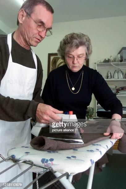 Helmut Schlegel läßt sich von der Hauswirtschaftsmeisterin Annie Zierz in der Augsburger Hauswirtschaftsschule im Bügeln unterrichten Schlegel ist...