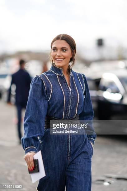 Heloise Agostinelli wears a blue denim jumpsuit a leather belt outside Dior during Paris Fashion Week Womenswear Fall/Winter 2020/2021 on February 25...
