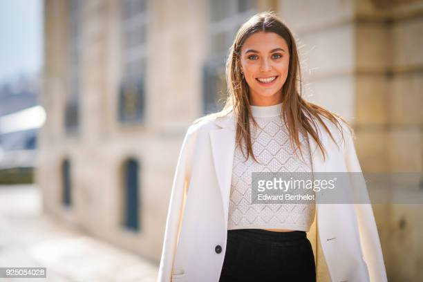 Heloise Agostinelli wears a white coat a white lace top black pants a bag outside Dior during Paris Fashion Week Womenswear Fall/Winter 2018/2019 on...