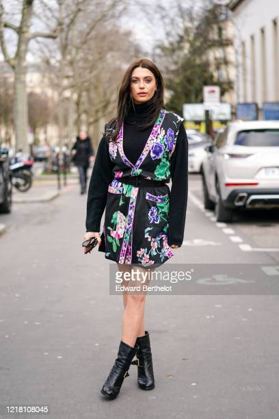 Heloise Agostinelli wears earrings a black turtleneck pullover a black green and purple floral print kimono dress a belt black leather boots outside...