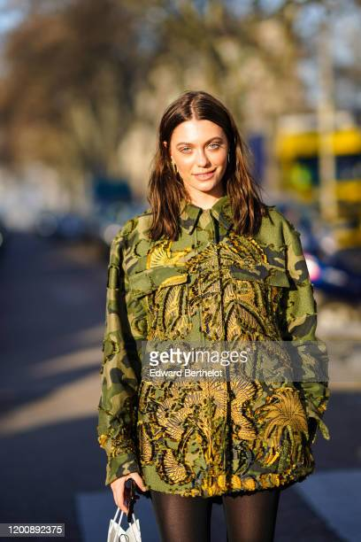 Heloise Agostinelli wears earrings a khaki print shirt with embroideries outside Dior during Paris Fashion Week Haute Couture Spring/Summer 2020 on...