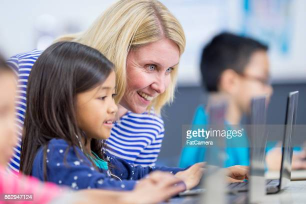 help from teacher - kids reading in classroom stock pictures, royalty-free photos & images