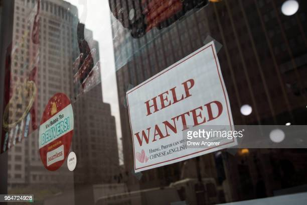 A 'help wanted' sign hangs on a window of a restaurant in Lower Manhattan May 4 2018 in New York City US unemployment fell to a near historic low of...
