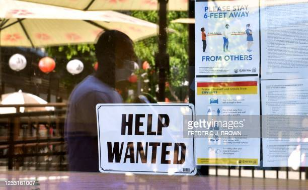 Help Wanted' sign is posted beside Coronavirus safety guidelines in front of a restaurant in Los Angeles, California on May 28, 2021. - Following...