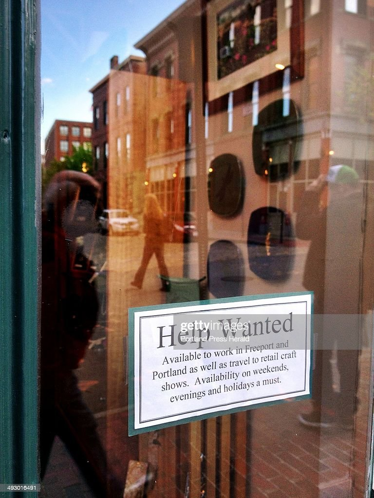 A help wanted sign on the door of Lovell Designs in