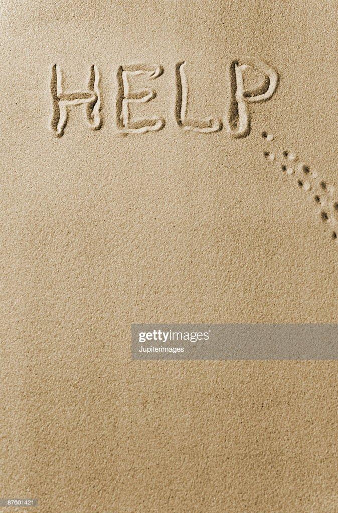 Help written in sand : Stock Photo