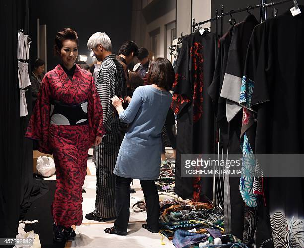 Helped by staffs models wear Kimonos backstage during the 2015 spring/summer collection by Sansai Saito and Jotaro Saito in the Tokyo Fashion Week on...