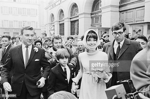 Helped by Swiss policemen, actress Audrey Hepburn and her husband, Italian psychiatrist Dr. Andrea Dotti, make their way through a crowd of newsmen...