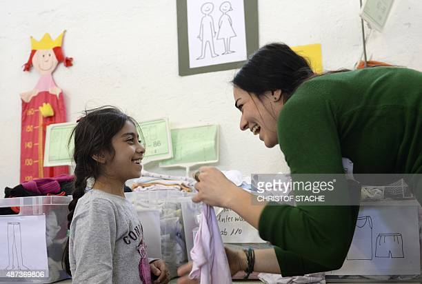 A helper and a migrant girl from Syria laugh in 'Bayernkaserne' where donations for refugess have been collected in Munich southern Germany on...