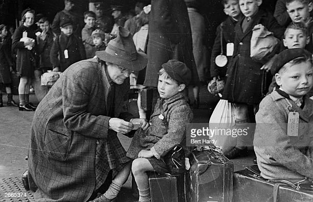 Helper at Paddington Station in London fixing a label onto a child being evacuated from London during the war. Original Publication: Picture Post -...