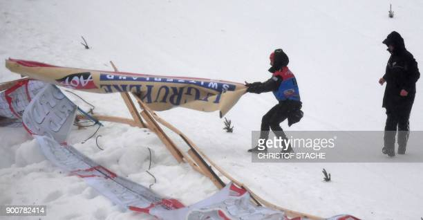 A helper holds an advertising banner torn off from the wind at the ski stadion where the sprint classic style event of the 'Tour de Ski' Cross...