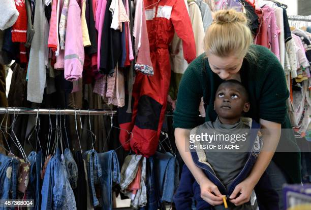 A helper puts a jacket at a refugee boy at the 'Bayernkaserne' where clothes for migrants have been collected in Munich southern Germany on September...