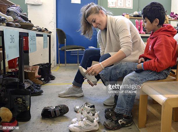 A helper puts a shoe at a foot of a Syrian refugee boy at the 'Bayernkaserne' where donations for migrants have been collected in Munich southern...