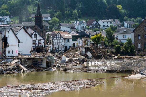 Helper uses an excavator to load house debris onto a truck behind the river Ahr one week after the after the devastating flood disaster on July 23,...