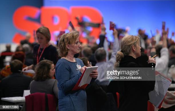 Helpers count the votes as delegates of Germany's social democratic SPD party hold up their voting cards during an extraordinary SPD party congress...