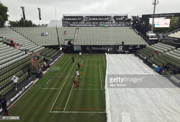Helpers cover the Center Court to protect the grass from the heavy rain during day 2 of the Mercedes Cup at Tennisclub Weissenhof on June 12 2018 in...