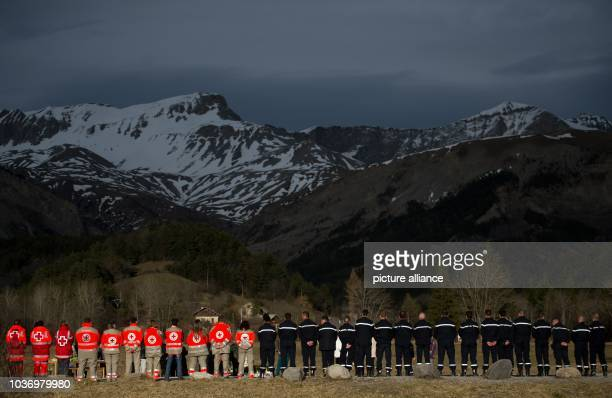 Helpers from the French Red Cross and police stand at the memorial plaque for the victims of the Germanwings A320 crash in Le Vernet France 28 March...