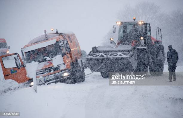 Helpers in a wheel loader try to pull back on the road a truck that has slipped off the track due to heavy snowfall on January 18 2018 near...