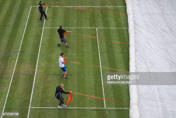 Helpers pull a tarp over the Center Court at the start of a downpour during the ATP Mercedes Cup tennis tournament in Stuttgart, southwestern...