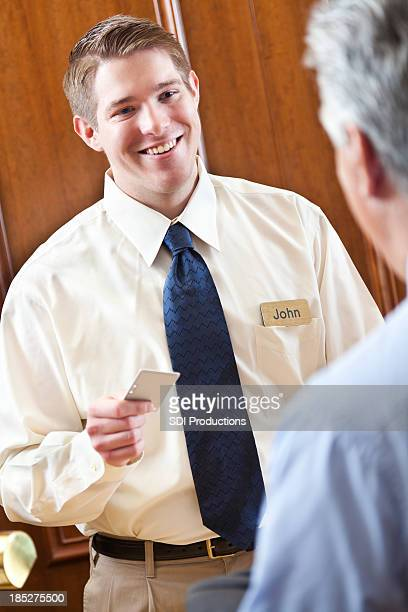 Helpful hotel worker handing room key to guest