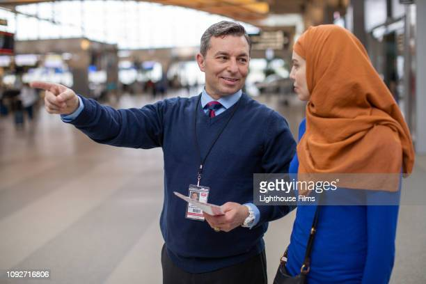 helpful ticket agent gives directions to middle eastern woman in airport lobby. - judaism stock pictures, royalty-free photos & images