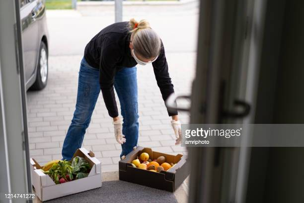 helpful woman neighbor delivering fresh food at doorstep during coronavirus crisis - social distancing stock pictures, royalty-free photos & images